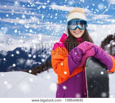 winter, leisure, sport and people concept - happy young woman in ski goggles with snowboard over snow and mountain background