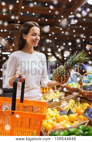 sale, shopping, consumerism and people concept - happy young woman with food basket in market over snow effect