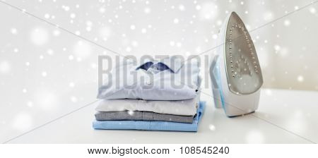 ironing, clothes, housework and objects concept - close up of iron and clothes on table at home over snow effect