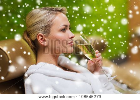 people, beauty, lifestyle, holidays and relaxation concept - beautiful young woman in white bath robe lying on chaise-longue and drinking champagne at spa with snow effect