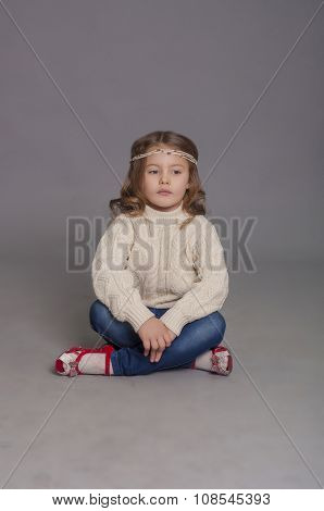 Little girl in white sweater and  jeans