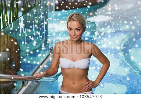 people, beauty, spa, healthy lifestyle and relaxation concept - beautiful young woman in bikini swimsuit raising upstairs in swimming pool with snow effect