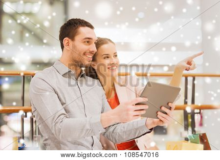 sale, consumerism, technology and people concept - happy young couple with shopping bags and tablet pc computer pointing finger in mall with snow effect