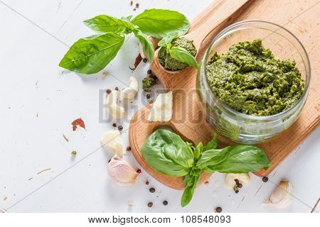 Pesto sause and ingredients on white background