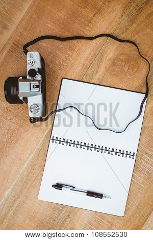 View of an old camera and a notebook on wood desk