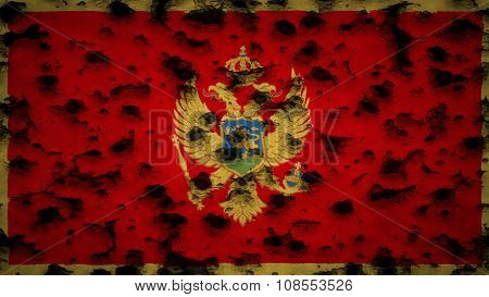 Flag of Montenegro painted on wall with bullet holes