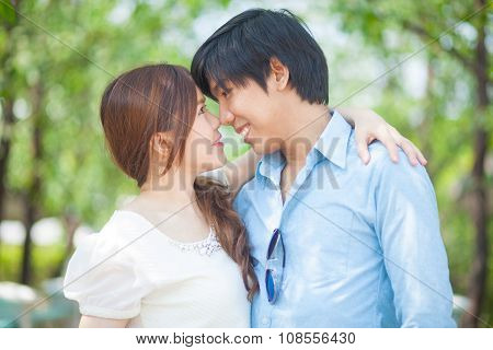 Loving Asian Couple Under Tree In The Park