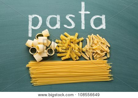 various uncooked pasta on green chalkboard