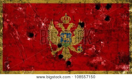 Flag of Montenegro painted on metal with bullet holes