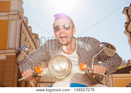 Handsome Happy Man With Sunglasses Riding A Motorbike