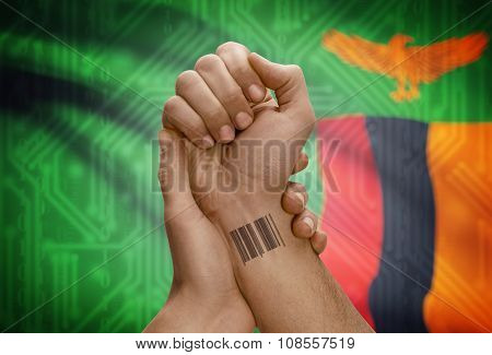 Barcode Id Number On Wrist Of Dark Skinned Person And National Flag On Background - Zambia