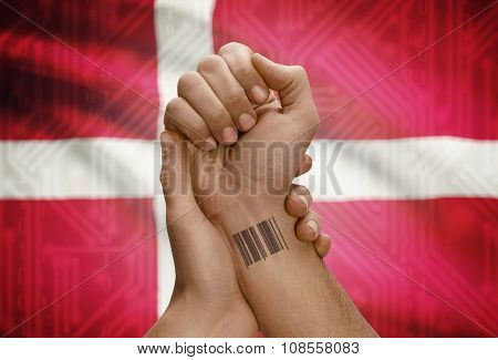 Barcode Id Number On Wrist Of Dark Skinned Person And National Flag On Background - Denmark