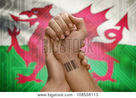 Barcode Id Number On Wrist Of Dark Skinned Person And National Flag On Background - Wales
