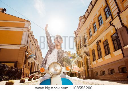 Handsome Cheerful Man Riding A Motorbike Picking Up One Hand