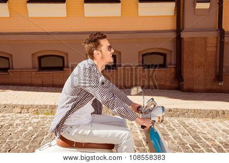 Side View Of A Handsome Man Riding A Motorbike