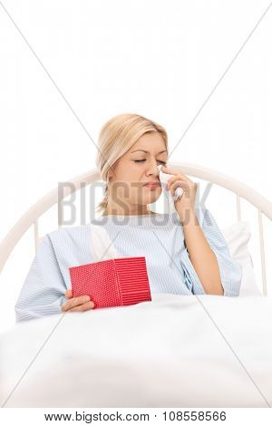 Vertical shot of a sad female patient lying in a hospital bed and crying isolated on white background