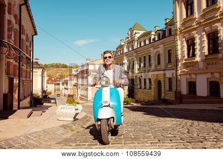 Handsome Cheerful Man Riding A Scooter On The Street