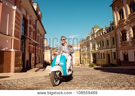 Handsome Man With Glasses Riding A Scooter On The Street