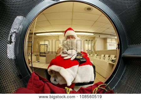 Santa Claus washes his own clothes at the Laundromat before Christmas. Focus on Santa's Clothes. Shot with a Fish eye Lens from the Inside out for a Unique and Funny View unseen by anyone until now.