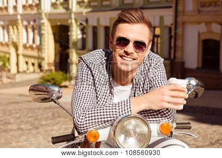 Young Handsome Man Standing Near The Scooter Holding A Cup Of Coffee