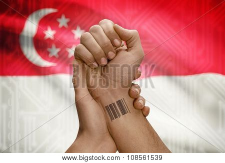 Barcode Id Number On Wrist Of Dark Skinned Person And National Flag On Background - Singapore