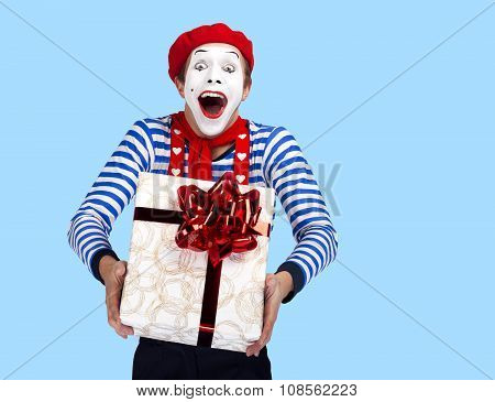Mime with present.Emotional funny actor wearing sailor suit, red beret posing on blue background.