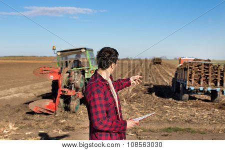 Farmer On Field With Tractors That Working