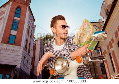 Happy Handsome Young Man With Glasses Sitting On The Motorbike Looking At The Map
