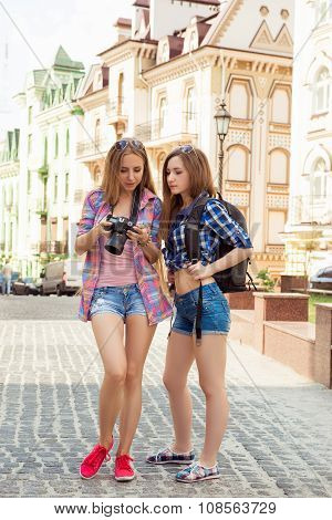 Two Pretty Young Tourists Looking At The Screen Of A Camera