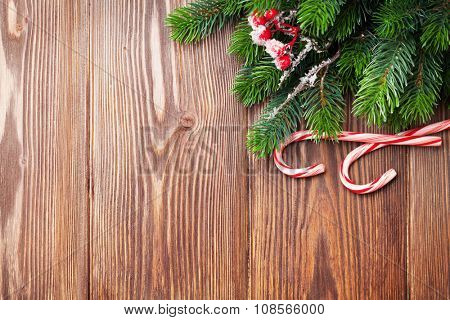 Candy cane and christmas tree on wooden table. View with copy space