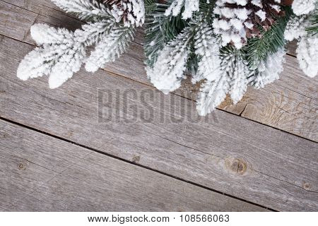 Fir tree covered with snow on wooden board