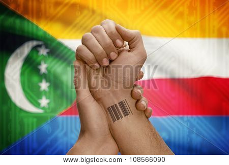 Barcode Id Number On Wrist Of Dark Skinned Person And National Flag On Background - Comoros