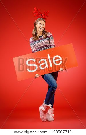 Cheerful pretty young woman wearing Christmas deer horns holding sale board. Beauty, fashion. Shopping. Full length portrait.