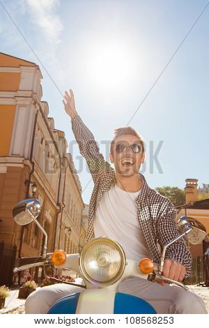 Handsome Happy Man Riding A Motorbike Picking Up One Hand