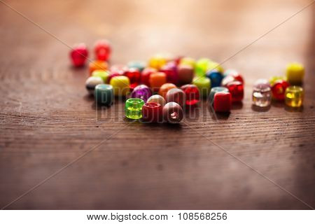 Colorful beads on old wooden work table, with incoming window light. Intentionally shot in Shallow depth of field and low key muted tone.