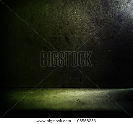 Concrete wall and floor with greenish lighting.