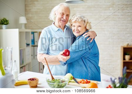 Happy senior husband and wife in embrace looking at camera in the kitchen