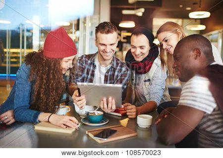 Teenage friends with touchpad looking at its screen while sitting in cafe