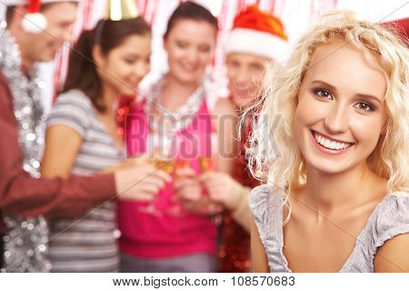 Blond girl looking at camera with toothy smile on background of toasting friends