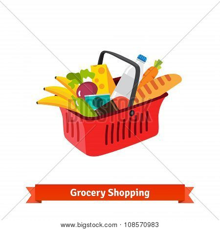 Red plastic shopping basket full of groceries