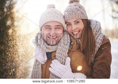Joyful dates in winterwear looking at camera while enjoying leisure