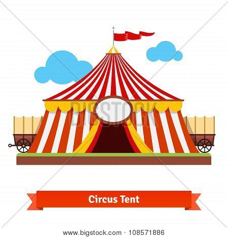 Open circus tent with wagon wheel in the back