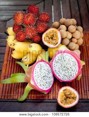 Assortment of tropical exotic fruits: dragonfruit, bananas, passion , longan, rambutan
