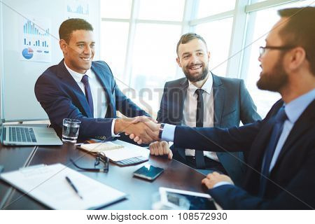 Happy businessmen handshaking after negotiation in office