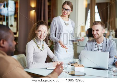 Group of managers looking at colleague at meeting