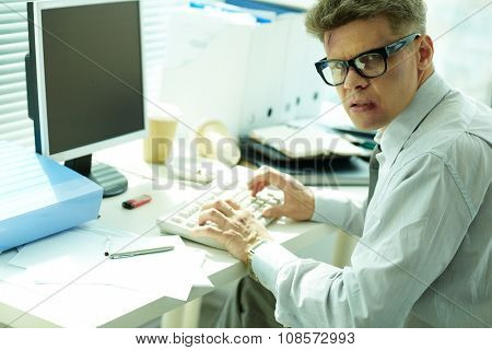 Businessman with bruised face looking at camera while typing