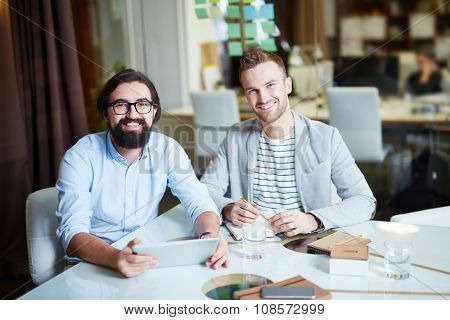 Two young businessmen looking at camera with smiles