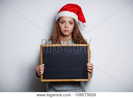 Sulky girl in Santa cap showing empty blackboard