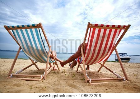 Couple holding hands and sunbathing on the beach
