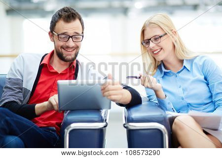 Cheerful business colleagues using touchpad for working